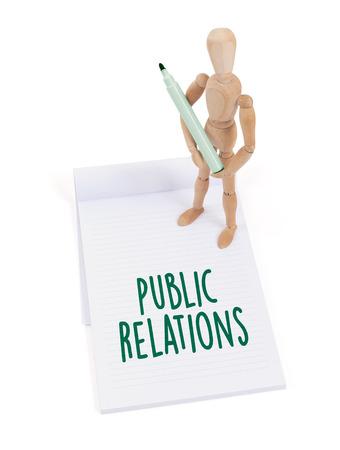 relaciones publicas: Maniquí de madera escribiendo en un bloc de notas - Relaciones públicas Foto de archivo