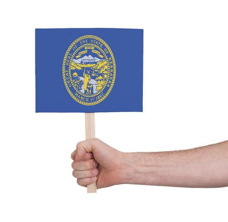 nebraska: Hand holding small card, isolated on white - Flag of Nebraska Stock Photo