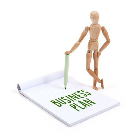 artists dummy: Wooden mannequin writing in a scrapbook - Business plan Stock Photo