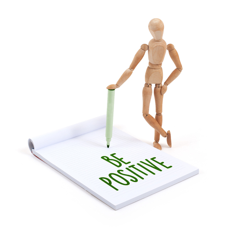 artists dummy: Wooden mannequin writing in a scrapbook - Be positive