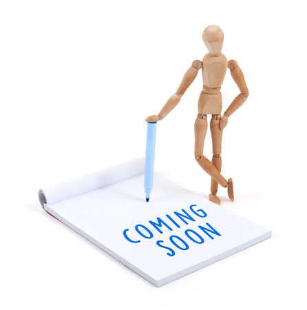 artists dummies: Wooden mannequin writing in a scrapbook - Coming soon Stock Photo