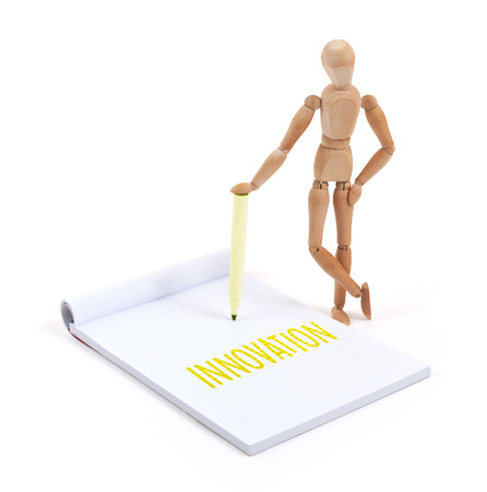 artists dummies: Wooden mannequin writing in a scrapbook - Innovation Stock Photo