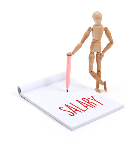 artists dummies: Wooden mannequin writing in a scrapbook - Salary Stock Photo