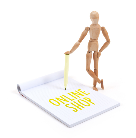 artists dummy: Wooden mannequin writing in a scrapbook - Online shop Stock Photo