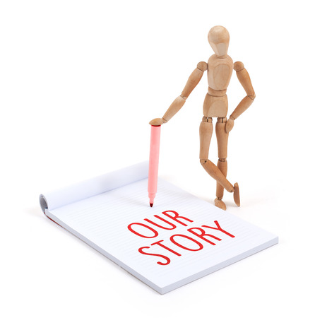 artists dummies: Wooden mannequin writing in a scrapbook - our story Stock Photo