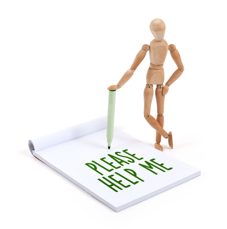 help me: Wooden mannequin writing in a scrapbook - Please help me Stock Photo