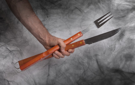 covert: Hand hold of BBQ equipment, covert in smoke Stock Photo
