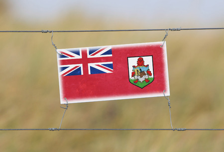 bermuda: Border fence - Old plastic sign with a flag - Bermuda