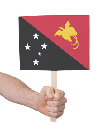 new guinea: Hand holding small card, isolated on white - Flag of Papua New Guinea