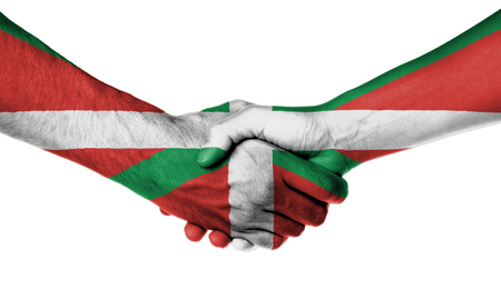 basque woman: Man and woman shaking hands, wrapped in flag pattern, Basque Country Stock Photo