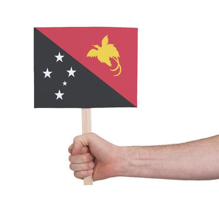 Nuova Guinea: Hand holding small card, isolated on white - Flag of Papua New Guinea