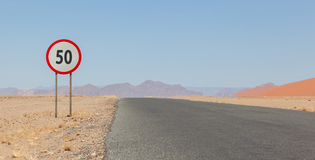 mph: Speed limit sign at a desert road in Namibia, speed limit of 50 kph or mph