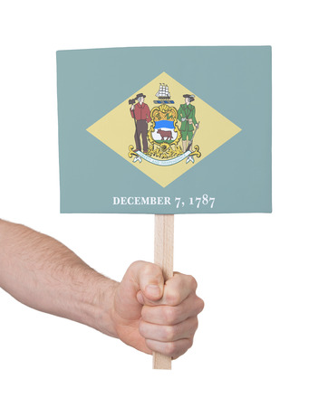 delaware: Hand holding small card, isolated on white - Flag of Delaware