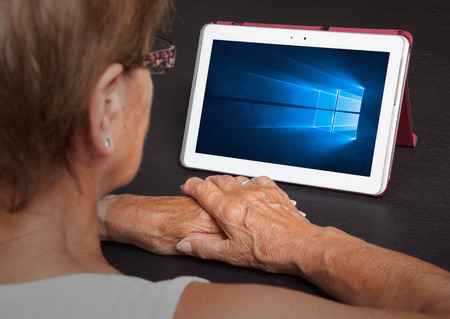os: HEERENVEEN, NETHERLANDS, June 6, 2015: Tablet computer with Windows 10 background. Windows 10 is the new version of Windows OS by Microsoft Corporation; it starting July 29, 2015.