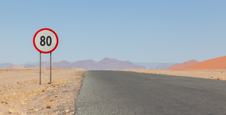 kph: Speed limit sign at a desert road in Namibia, speed limit of 80 kph or mph Stock Photo