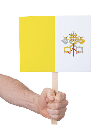 vatican city: Hand holding small card, isolated on white - Flag of Vatican City Stock Photo