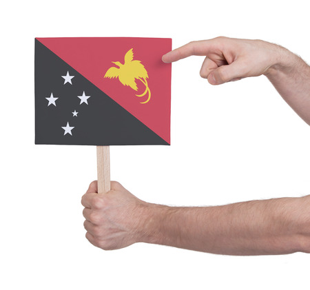 papua new guinea: Hand holding small card, isolated on white - Flag of Papua New Guinea