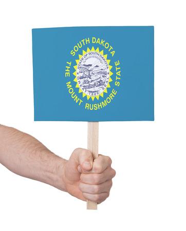 south dakota: Hand holding small card, isolated on white - Flag of South Dakota Stock Photo