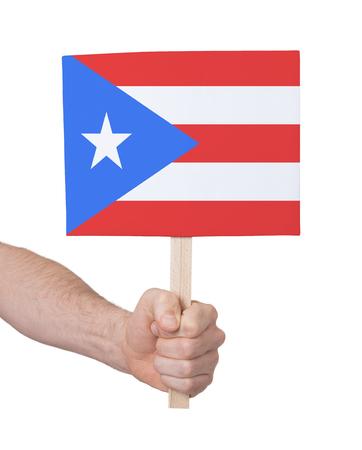 bandera de puerto rico: Mano que sostiene la peque�a tarjeta, aislado en blanco - la bandera de Puerto Rico