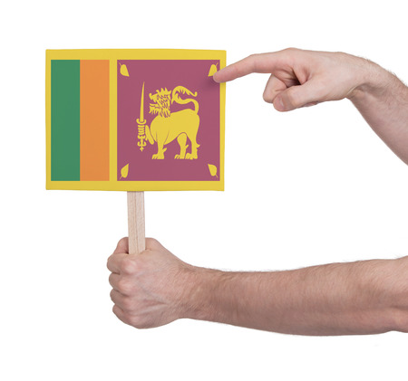 sri lankan flag: Hand holding small card, isolated on white - Flag of Sri Lanka