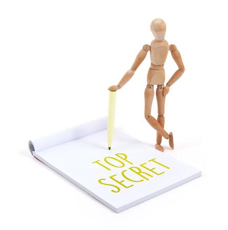 artists dummy: Wooden mannequin writing in a scrapbook - Top secret Stock Photo