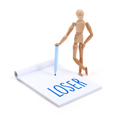 loser: Wooden mannequin writing in a scrapbook - Loser Stock Photo