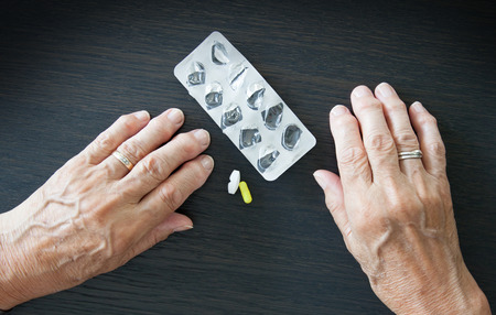instruction sheet: Elderly person taking medication, two different pills Stock Photo