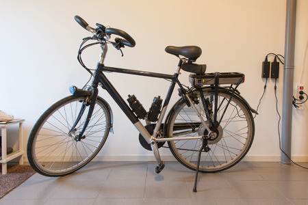 plug electric: Electric bicycle in a garage, charging the battery Stock Photo