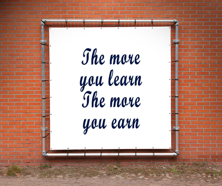 earn more: Large banner with inspirational quote on a brick wall - The more you learn the more you earn