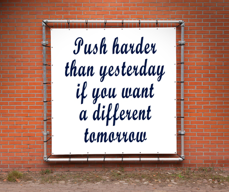 yesterday: Large banner with inspirational quote on a brick wall - Push harder than yesterday... Stock Photo
