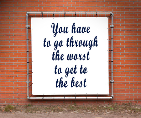 worst: Large banner with inspirational quote on a brick wall - You have to go through the worst...