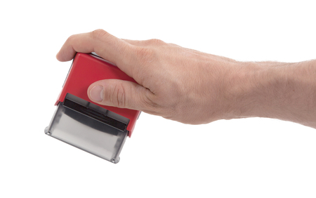 red stamp: Plastic stamp in hand, isolated on white