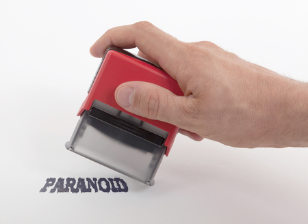 paranoid: Plastic stamp in hand, isolated on white - Paranoid