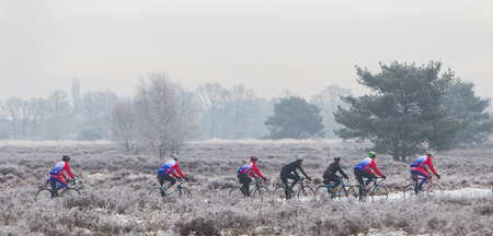 tiring: EPE, THE NETHERLANDS - MARCH 5, 2016: Cyclists under winter skies on a training ride in order to regain the fitness lost over the holidays.