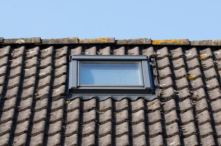 dormer: Modern dormer on a black tiled roof Stock Photo
