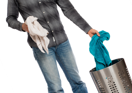 man laundry: Young man putting a dirty towel in a laundry basket, isolated