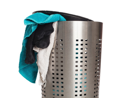 Dirty laundry in a metal basket, isolated on a white background Stock Photo