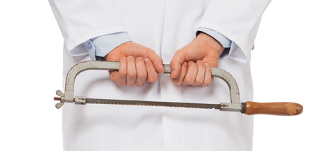 amputation: Crazy doctor is holding a big saw in his hands, isolated on white Stock Photo