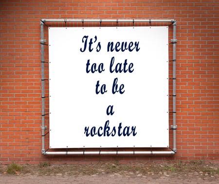llegar tarde: Gran pancarta con la cita inspirada en una pared de ladrillo - Nunca es demasiado tarde para ser una estrella de rock