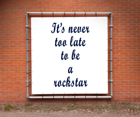 too late: Large banner with inspirational quote on a brick wall - Its never too late to be a rockstar