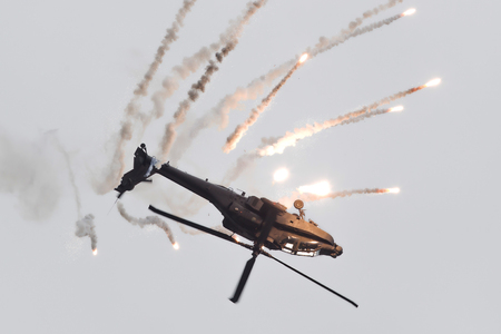 heli: LEEUWARDEN, THE NETHERLANDS - JUN 11, 2016: Boeing AH-64 Apache attack helicopter flying a demo during the Royal Netherlands Air Force Days