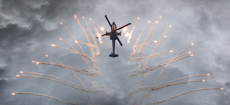heli: Silhouette of an attack helicopter firing flares, storm is coming Editorial