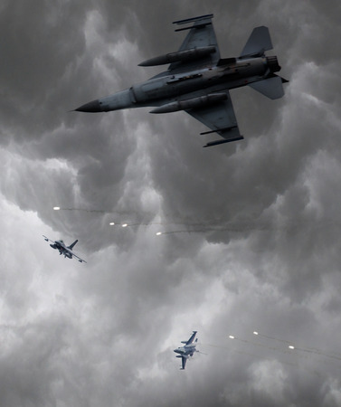 Military jets firing of flares, stormy sky, selective focus Stock Photo