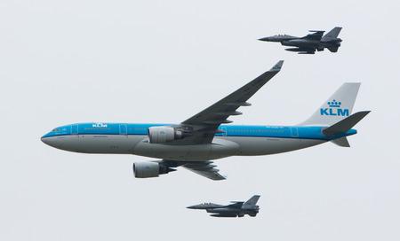 LEEUWARDEN, NEDERLAND - 11 juni 2016: Nederlandse KLM Boeing geëscorteerd door twee F16 straaljagers van de Nederlandse luchtmacht op juni 11, 2016 in Leeuwarden. Redactioneel