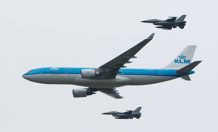 LEEUWARDEN, NETHERLANDS - JUNE 11 2016: Dutch KLM Boeing escorted by two F16 fighter jets of the Dutch air force on juni 11 , 2016 in Leeuwarden.
