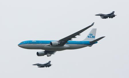 LEEUWARDEN, NEDERLAND - 11 juni 2016: Nederlandse KLM Boeing geëscorteerd door twee F16 straaljagers van de Nederlandse luchtmacht op juni 11, 2016 in Leeuwarden.