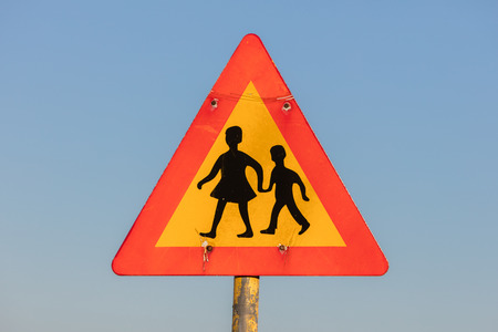 crossing street: warning sign of children crossing street from school Stock Photo