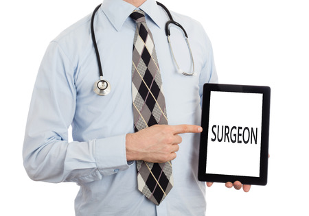 healthcare facilities: Doctor, isolated on white background, holding digital tablet - Surgeon Stock Photo