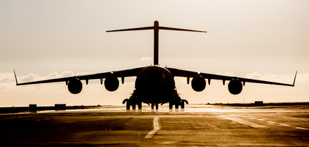 airstrip: Large military cargo plane silhouette on an empty airstrip