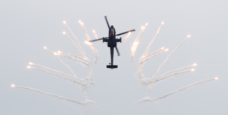 apache: LEEUWARDEN, THE NETHERLANDS - JUN 11, 2016: Dutch AH-64 Apache attack helicopter firing off flares during the Royal Netherlands Air Force Days